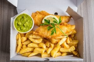 fish and chips with peas and slice of lemon and royalty free image 884635802 1548434060